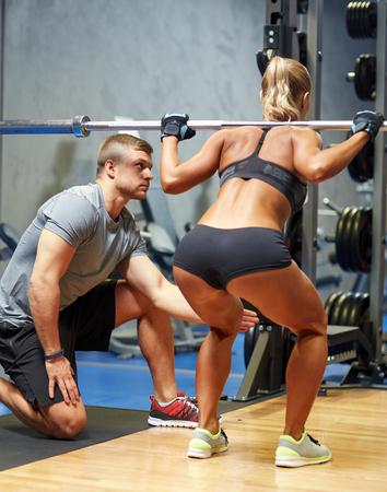 hombres trabajando: deporte, gimnasio, trabajo en equipo, el culturismo y la gente concepto - mujer joven y entrenador personal con barra flexionando los músculos en el gimnasio