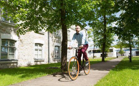 clavados: personas, estilo, ocio y estilo de vida - feliz joven inconformista montar en bicicleta de piñón fijo en la calle de la ciudad Foto de archivo