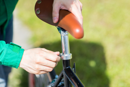 setting: people, vehicle, eisure and lifestyle - close up of man adjusting fixed gear bike saddle high Stock Photo