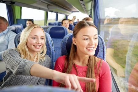 le transport, le tourisme, l'amitié, voyage sur la route et les gens concept - les jeunes femmes ou amies adolescentes équitation dans le bus de Voyage