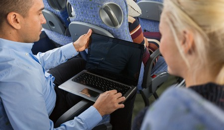 shuttle: transport, tourism, road trip, technology and people concept - close up of passengers couple with laptop in travel bus