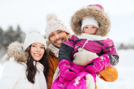 clothes winter: parenthood, fashion, season and people concept - happy family with child in winter clothes outdoors