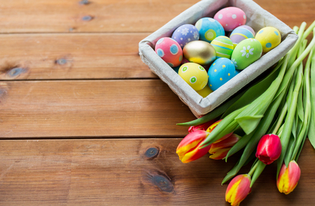easter, holidays, tradition and object concept - close up of colored easter eggs in basket and tulip flowers
