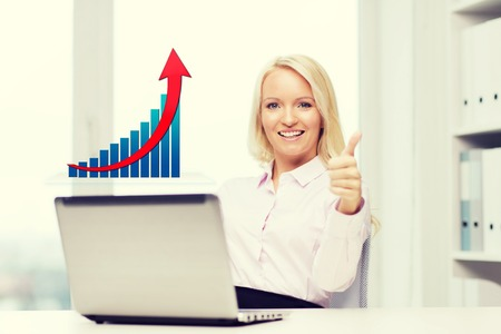 growing business: business, success, people, gesture and technology concept - smiling businesswoman showing thumbs up with laptop computer and growing chart in office