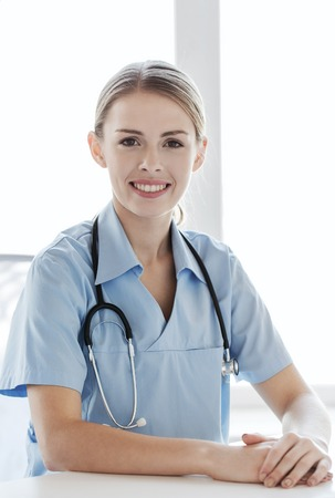 health care and medicine: health care, profession, people and medicine concept - happy female doctor or nurse with clipboard at hospital Stock Photo