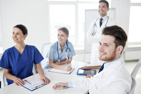 medical education: medical education, health care, medical education, people and medicine concept - group of happy doctors or interns with mentor meeting on presentation at hospital