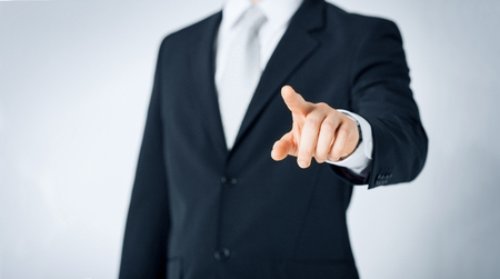 people, business and gesture concept - close up of man pointing finger to to something