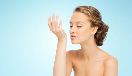 perfume woman: beauty, aroma, people and body care concept - young woman smelling perfume from wrist of her hand over blue background Stock Photo