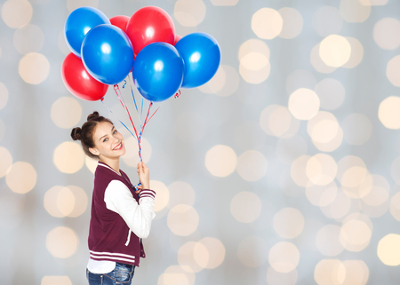 helium: people, teens, holidays and party concept - happy smiling pretty teenage girl with helium balloons over lights background