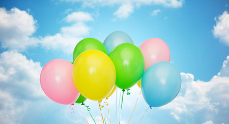 inflated: holidays, birthday, party and decoration concept - bunch of inflated colorful helium balloons over blue sky and clouds background