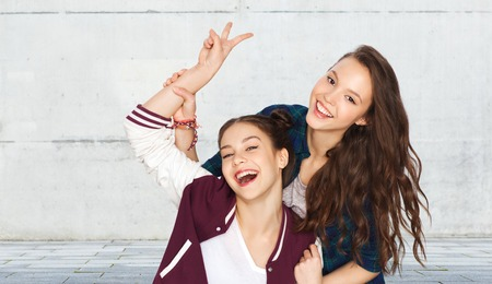 amigos abrazandose: people, friends, teens and friendship concept - happy smiling pretty teenage girls showing peace hand sign over gray urban street background