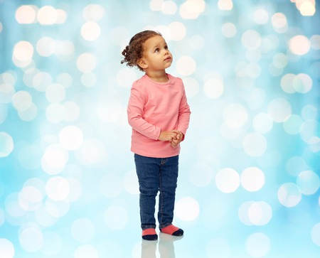 baby blue: childhood, fashion, clothing and people concept - beautiful african american little baby girl portrait over blue holidays lights background