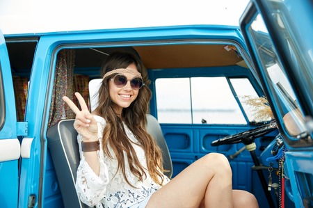 mujer hippie: summer holidays, road trip, vacation, travel and people concept - smiling young hippie woman showing peace gesture in minivan car Foto de archivo