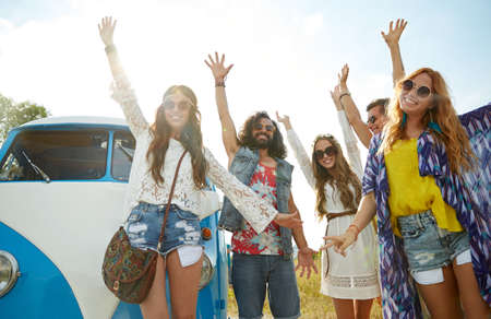 trip over: summer holidays, road trip, vacation, travel and people concept - smiling young hippie friends having fun over minivan car