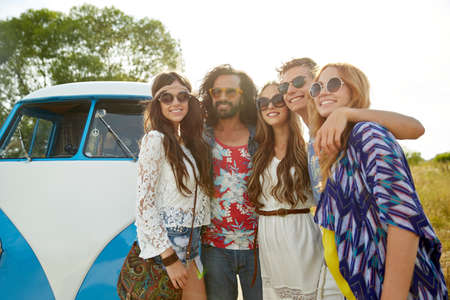 minivan: summer holidays, road trip, vacation, travel and people concept - smiling young hippie friends over minivan car