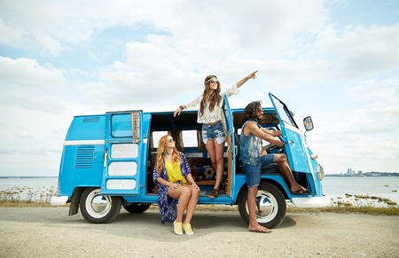 summer holidays, road trip, vacation, travel and people concept - smiling young hippie friends in minivan car on beach Stock Photo