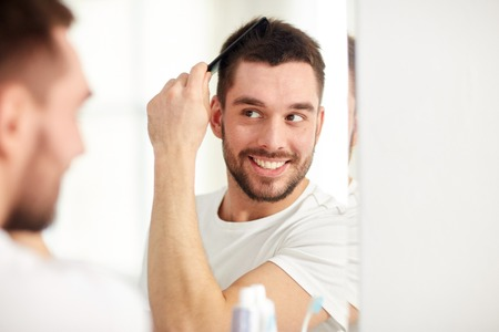 Schönheit, Pflege und Menschen Konzept - lächelnden jungen Mann auf Spiegel und Haare bürsten mit Kamm zu Hause Badezimmer