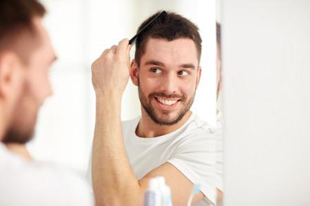 schoonheid, verzorging en mensen concept - glimlachende jonge man op zoek naar spiegel en borstelen haar met kam thuis badkamer