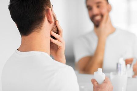 viso uomo: bellezza, cura della pelle e persone Concetto - Primo piano del giovane sorridente applicare la crema su viso e guardando a specchio in bagno di casa