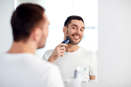 electric razor: beauty, hygiene, shaving, grooming and people concept - young man looking to mirror and shaving beard with trimmer or electric shaver at home bathroom