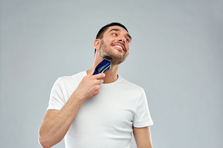 electric shaver: beauty, grooming and people concept - smiling young man shaving beard with trimmer or electric shaver over gray background Stock Photo