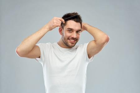아름다움, 손질 및 사람들이 개념 - 회색 배경 위에 빗 머리를 칫 솔 질하는 젊은이 미소