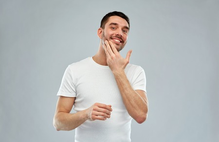 aftershave: beauty, skin care, body care and people concept - smiling young man applying cream or lotion to face over gray background Stock Photo