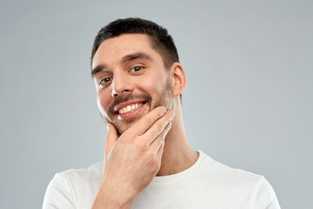 male face: beauty, skin care, grooming and people concept - happy young man touching his face or beard over gray background
