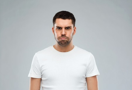 funny face: emotion, fun and people concept - man with funny angry face over gray background Stock Photo