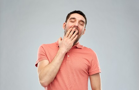 bedtime: rest, bedtime and people concept - tired yawning man over gray background Stock Photo