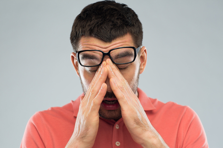 eyesight: people, eyesight, stress, overwork and problem concept - tired man in eyeglasses rubbing his eyes