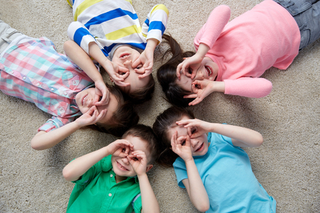 childhood, fashion, friendship and people concept - happy children making faces and having fun lying on floor in circle