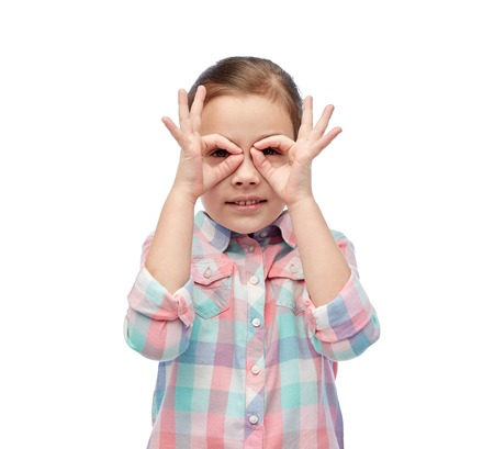 glasses eye: childhood, fun, gesture and people concept - happy little girl making faces Stock Photo
