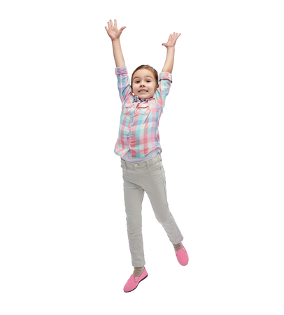 hispanic girl: happiness, childhood, freedom, movement and people concept - happy little girl jumping in air Stock Photo