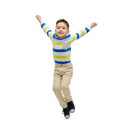 air movement: happiness, childhood, freedom, movement and people concept - happy little boy jumping in air Stock Photo