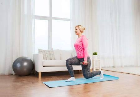 squats: fitness, sport, training and lifestyle concept - smiling woman with dumbbells exercising and doing squats at home