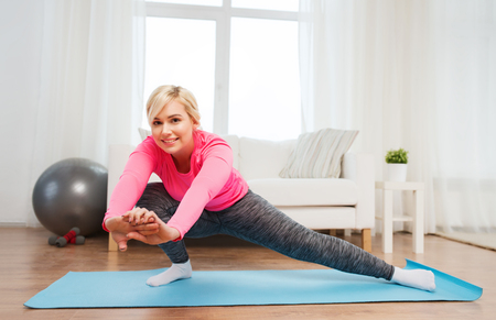 woman stretching: fitness, sport, people and healthy lifestyle concept - happy plus size woman stretching leg on mat at home