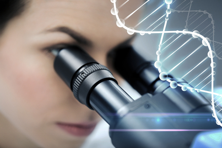 eyepiece: science, chemistry, technology, biology and people concept - close up of young female scientist looking to microscope eyepiece and making research in clinical laboratory with dna molecule structure Stock Photo