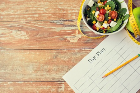 Gesunde Ernährung, Diät, Abnehmen und Gewicht Verlust Konzept - Großaufnahme von Diät-Plan Papier grüner Apfel, Maßband und Salat Standard-Bild - 59228113