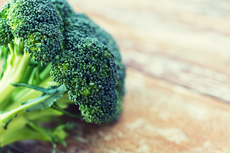 vegetarian food: healthy eating, diet, vegetarian food and culinary concept - close up of broccoli on wooden table Stock Photo