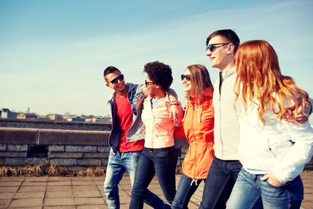 going: tourism, travel, people and leisure concept - group of happy teenage friends walking along city street and talking