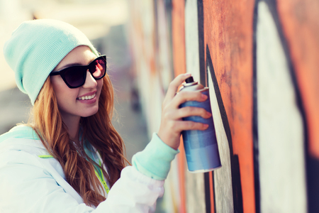 Graffiti: people, art, creativity and youth culture concept - young woman or teenage girl drawing graffiti with spray paint on street wall Stock Photo