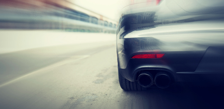 car exhaust: transportation, speed, racing and road concept - close up of car riding on highway from back