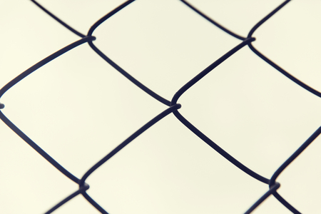 detain: captivity, prison and obstruction concept - close up of mesh fence over gray sky Stock Photo