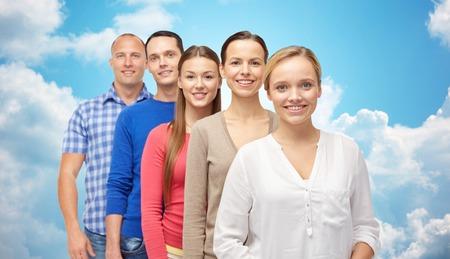 fila de personas: la familia, el género y el concepto de personas - grupo de la sonrisa hombres y mujeres de más de cielo azul y las nubes de fondo