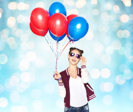 memorial: people, teens, holidays, party and summer concept - happy smiling pretty teenage girl in sunglasses with helium balloons over blue holidays lights background