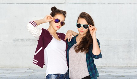 street fashion: people, friendship, fashion, summer and teens concept - happy smiling pretty teenage girls in sunglasses over urban street background
