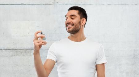 perfumery concept: perfumery, beauty and people concept - happy smiling young man with male perfume over gray stone wall background