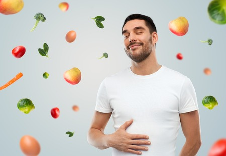 food, healthy eating, diet and people concept - happy full man touching his tummy over gray background with falling fruits