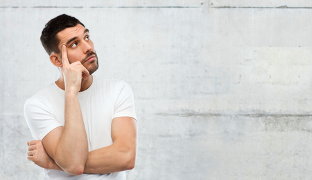 doubt, expression and people concept - man thinking over gray stone wall background